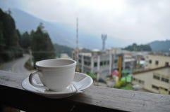 Relájese con una taza de café caliente por mañana brumosa en una montaña adentro Imagen de archivo