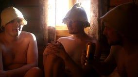 Relájese en el baño para tres amigos, sentándose en una ventana con el sol bebiendo una cerveza fría para la conversación 3840x21 almacen de metraje de vídeo