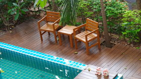 Relájese en el lado de la piscina en el jardín Imágenes de archivo libres de regalías
