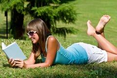 Relájese en el parque - mujer con el libro en día asoleado Fotografía de archivo libre de regalías