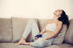 Relájese en la mujer adolescente del sofá que miente con la taza Foto de archivo libre de regalías