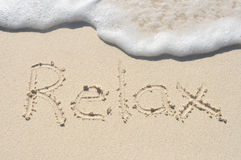 Relájese escrito en arena en la playa Fotos de archivo libres de regalías