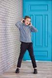 Relájese y concepto de la música que escucha Terraplén europeo del muchacho el pedazo Muchacho en ropa de sport Imagen de archivo libre de regalías