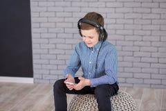 Relájese y concepto de la música que escucha Terraplén europeo del muchacho el pedazo Muchacho en ropa de sport Imagen de archivo