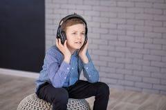 Relájese y concepto de la música que escucha Terraplén europeo del muchacho el pedazo Muchacho en ropa de sport Fotografía de archivo