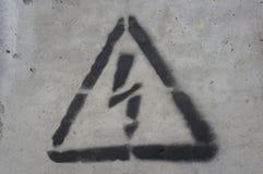 Relámpago negro en un triángulo en una superficie concreta Fotos de archivo libres de regalías
