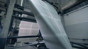 Relèvement de papier sur des rouleaux dans un bureau d'impression, fin banque de vidéos