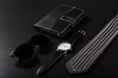 Relógio, caderno, óculos de sol, laço em um fundo preto Fotos de Stock Royalty Free