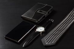 Relógio, caderno, telefone da venda, laço em um fundo preto Fotos de Stock Royalty Free