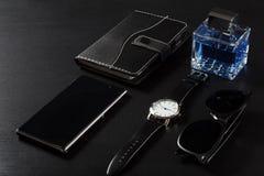 Relógio, caderno, telefone da venda, perfume do homem, óculos de sol em um preto Fotos de Stock Royalty Free