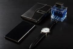 Relógio, caderno, telefone da venda, perfume do homem em um fundo preto Foto de Stock Royalty Free