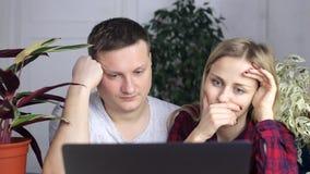 Relógio cansado e frustrante do indivíduo e da menina no monitor do portátil vídeos de arquivo
