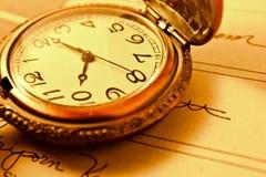 Relógio chain velho em um livro Fotos de Stock Royalty Free