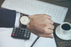 Relógio da mão do homem na tabela de funcionamento fotografia de stock royalty free