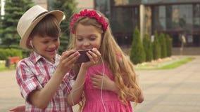 Relógio das crianças pequenas algo no smartphone fora foto de stock royalty free