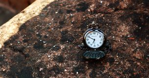 Relógio de bolso antigo na prateleira textured de pedra imagem de stock