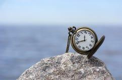 Relógio de bolso com mãos na pedra em um fundo azul Fotografia de Stock