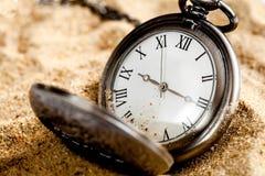 Relógio de bolso do conceito do fim do prazo no fundo da areia Foto de Stock