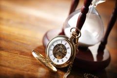 Relógio de bolso do ouro e hourglass foto de stock