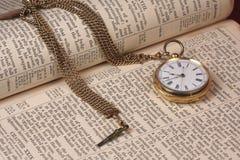Relógio de bolso do ouro na Bíblia velha imagens de stock