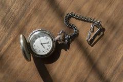 Relógio de bolso do vintage com sombra no fundo de madeira sob o feixe de luz imagem de stock royalty free