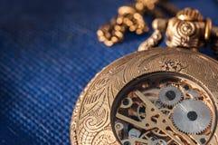 Relógio de bolso na tabela azul imagem de stock