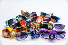 relógio de pulso e óculos de sol Multi-coloridos do ` s das mulheres em uma parte traseira do branco Fotos de Stock