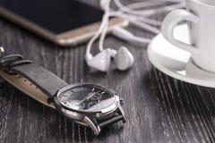 Relógio de pulso e telefone celular com fones de ouvido e uma xícara de café em uma tabela de madeira escura fotos de stock