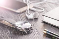 Relógio de pulso, telefone celular com fones de ouvido e um bloco de notas com uma pena em um desktop escuro velho do escritório fotografia de stock