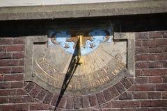 Relógio de sol em uma rua pública na cidade velha de Dordrecht, com uma diferença de 1 hora devido ao horário de verão imagem de stock