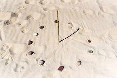 Relógio de sol na praia feita de uma vara e de pedras Relógio de sol no b imagem de stock royalty free