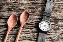 Relógio e colher de madeira na tabela Foto de Stock Royalty Free