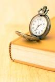 Relógio e livro velhos de bolso Imagem de Stock