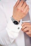 Relógio em uma mão no homem Imagens de Stock