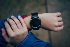 Relógio esperto na mão do ` s do menino Imagem de Stock