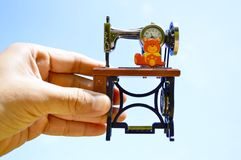 Relógio esquisito da máquina de costura disponível com fundo do céu azul Imagens de Stock Royalty Free