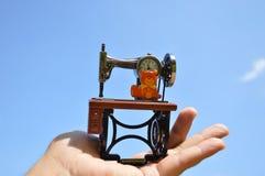 Relógio esquisito da máquina de costura na palma com céu azul Fotografia de Stock Royalty Free