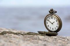 Relógio na pedra contra o mar, tempo Fotos de Stock Royalty Free