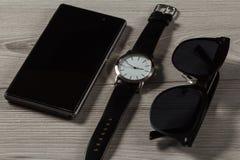 Relógio, telefone da venda, óculos de sol em um fundo de madeira cinzento Imagens de Stock