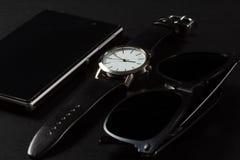 Relógio, telefone da venda, óculos de sol pretos em um fundo preto Imagens de Stock