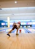 Relógios da menina atenta em rolos da esfera de bowling Fotografia de Stock Royalty Free