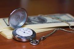 Relógios de bolso e muito cem dólares fotografia de stock