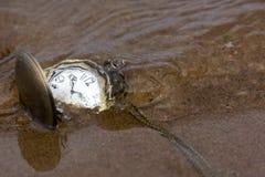 Relógios de bolso redondos na areia sob a água Imagem de Stock Royalty Free