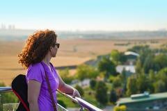 Relógios de cabelo vermelhos da mulher ao redor da torre de observação em Mogan Park imagens de stock royalty free