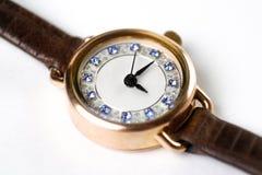 Relógios de ouro das mulheres em uma correia de couro Tiro do close-up Em um whit fotografia de stock
