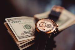 Relógios e 100 dólares de close up Imagens de Stock