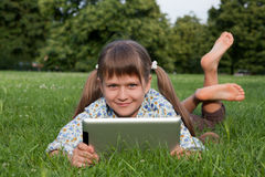 Rel sin hilos del ordenador de la tablilla de la explotación agrícola del niño de la muchacha Foto de archivo libre de regalías