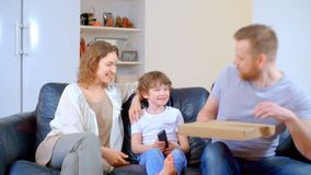 Relación de familia entre el hijo, el padre y la madre felices Ven la TV y prueban la pizza almacen de video
