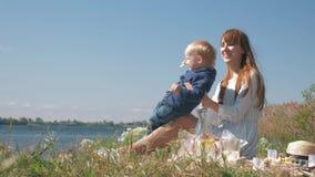 relación del Madre-niño, el jugar femenino alegre con el niño pequeño durante comida campestre de la familia en cierre de la natu almacen de metraje de vídeo