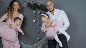 Relación feliz, mamá y papá con las pequeñas hijas en los brazos que presentan para la foto en fondo de la pared gris con grande almacen de video